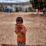 A boy looks on behind a net at the refugee camp of Schisto in Athens on June 8. Aris Messinis/AFP/Getty Images